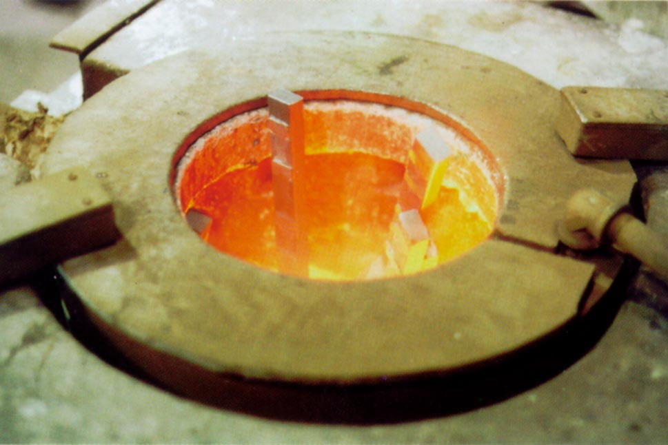 Molten metal blanketing of surface melt in crucible furnace within metal foundry operation